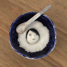 """Small salt dish set with a head floating in the middle.Each piece is hand built and painted by the artist.Dish: Approx. 3 3/4"""" w X 3 3/4"""" l X 1 1/4"""" hSpoon: Approx. 3/4"""" w X 3 1/2"""" l X 3/8"""" hFood safe.Please hand wash with care."""