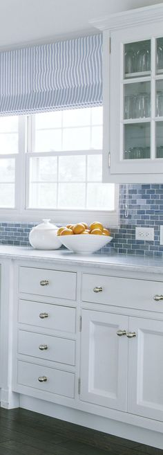 Blue tile backsplash in a coastal kitchen with white cabinets and silver hardware