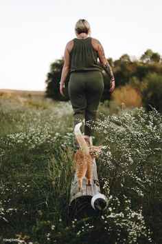 A cat following it's owner in a farm