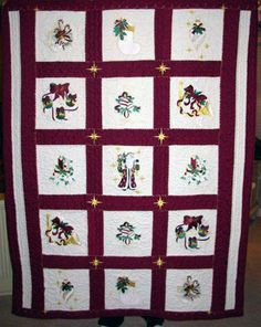 Quilt embroidered with bells, stockings, Santa, and other Christmas machine embroidery designs.