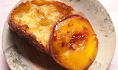 Half a caramel peach leaning against a crisp slice of brioche toast