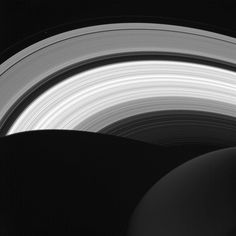 The bright rings of Saturn, cut by the dark shadow of the planet. The night side of Saturn is visible as a faint grey sphere, lit only by light reflected from the rings.