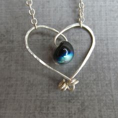 This whimsical necklace features a black dichroic (silver, blue) glass teardrop bead suspended on a sterling wire forged heart; it has a handforged back