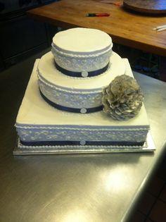 Handmade paper flower adorns traditional wedding cake.