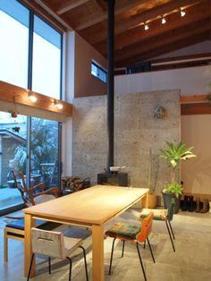 リビングダイニング事例:吹抜けの土間リビング(群馬県邑楽町・土間リビングの家|A house)この家の中心にある土間リビング。文字通り玄関からそのまま土足で入ります。床は全面コンクリート。薪ストーブの暖気は大きな吹抜けから2階へも伝わります。南面の大きなハイサイドライトから光と風と風景を取り込む明るい空間です。