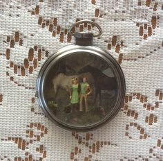 Young couple with horses necklace with miniature scene.