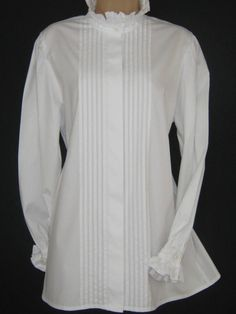 L A U R A A S H L E Y  I dont like ephemeral things, I like things that last forever  ~ Edwardian Lady ~   A CRISP WHITE VICTORIAN / EDWARDIAN STYLE COTTON BLOUSE WITH HIGH RUFFLE TRIMMED NECK. ELABORATELY ADORNED WITH FRONT VERTICAL PIN TUCKS, THE LONG SLEEVES ARE GATHERED INTO PERIOD STYLE PIN TUCKED, CIRCULAR RUFFLE CUFFS WHICH FASTEN WITH ONE BUTTON. THE FRONT BUTTON FASTENING IS CONCEALED WITH A FABRIC OVERLAP. THIS RARE, LONG-LENGTH BLOUSE IS OF CLASSIC, GENEROUS FIT AND SUITABLE F...