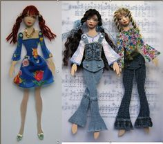 the bodies are 2 layers of cardstock stuck together, then old book pages stuck onto the back. The faces are molded from air dried clay and painted with acrylics. The features were colored in with water color pencils and the blush from chalks. The clothes are scraps of wool, lace and fibres. The hair is from braided hair bands bought in a charity shop. Artist cut the pieces off, glued them to the card head then unbraided what wasn't stuck down.