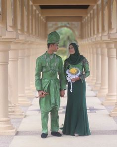 Malay weddings are usually colorful affairs, as demonstrated by this couple's matching emerald-hued ensembles.