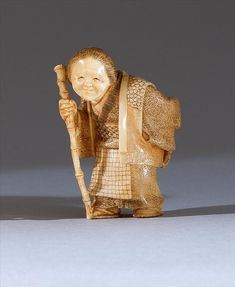 IVORY NETSUKE By Hogetsu. In the form of an elderly lady walking with a staff while holding prayer beads. Signed. Height 1.75""
