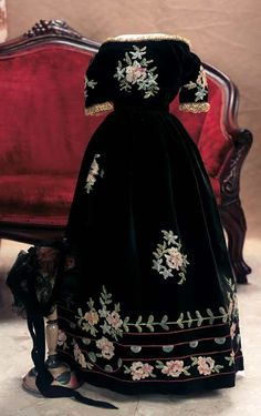 "Black Velvet Gown with Embroidered Flowers with Black Velvet and Lace Coiffe  5"" shoulder width. 11"" waist. 19"" overall length. A rich black silk/velvet fabric forms into a regal dress with rounded neckline and elbow-length sleeves trimmed with lace,hook and eye closures on the fitted bodice,gathered skirt,and having beautiful embroidery of dainty pastel flowers and vines.Circa 1870"