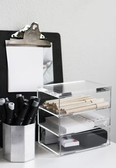 office organiser; 3 small cubes for pencil, post it note, ,.. .clipboard with paper and pen provided .silver cup with art pens (maybe)