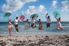 Classic beach wedding jump with parasol, Photo by Megan Tyjeski Photography