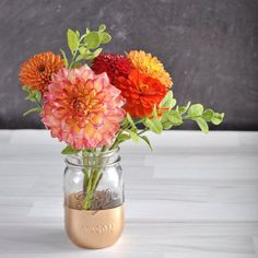 These gold-dipped mason jars are easy to make and would be perfect for a wedding centerpiece!