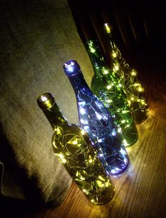 Wine bottles with white Christmas lights - the colors of the bottles don't need anything put a dark room and a plug.