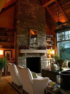 ..I like the rustic truck as a coffee table and the grey stone fireplace.  The white chairs with the brass tacks are a little too squared off to be considered really cozy though. Mantle decor lacks interest and is too symmetrical. Beautiful huge picture window!