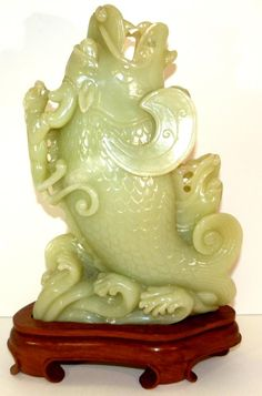 "CELEDON APPLE TRANSLUCENT JADEITE DRAGON KOI VASE Hand carved Chinese jadeite figural fish vase depicting two fish with dragon heads. Each is depicted jumping out of the water. Standing on the back of one fish is a foo lion. 19th century. Has fitted wooden base. Measures 12 3/4"" height + 2"" height"