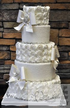 5 Tiered Buttercream Iced Wedding Cake; I'd add a little colour the ribbons; purple probably!