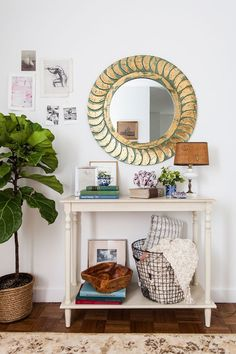 A weathered gold mirror above a foyer table.