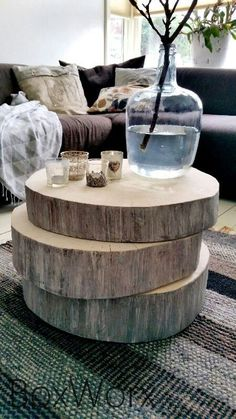 Giant wood slices stacked as a coffee table with accompanying vase, branches and candles, give this room a rustic feel.