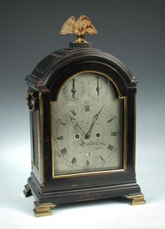 Sale F090316 Lot 681  A George III ebonised fruitwood bracket clock, the triple pad top with gilt metal eagle finial above break arch silvered 8inch (20cm) dial, signed to the centre 'John Williams, London', seconds and strike/silent dials above, date aperture below, shaped hands, twin fusee movement with anchor escapement and engraved backplate, adjustable pendulum with holdfast screw, glazed rear door, side handles above pierced scale frets, upon gilt ogee feet, h:52 w:31.50 cm  - Cheffins