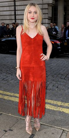 Dakota Fanning wears Valentino red fringe dress with studded pumps and bright red lips to match.