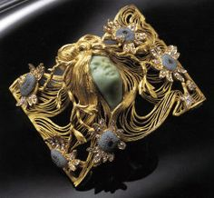 Lalique 1900 signed Plaque De Cou: arched plaque w/ a central carved chrysophrase woman's head framed by openwork flowing hair to the entire area, w/fine superimposed diamond & enamel sunflowers; 12 side hooks for choker. Description: christies.com