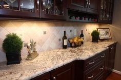 Light tile backsplash set on an angle to go with the Giallo Ornamental granite and dark cabinets.
