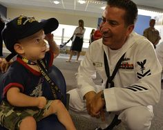 Hospital Corpsman 2nd Class Charles Landry, assigned to Navy Operational Support Center Austin, gives a boy a Navy ball cap at the Children's Hospital in Boston as part of Caps for Kids during Boston Navy Week. (U.S. Navy photo by Mass Communication Specialist 2nd Class Kathryn E. Macdonald/Released)