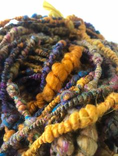 Hand spun recycled sari silk and Merino art yarn Core spun around an ecological produced woolen core yarn and plied into super coils.