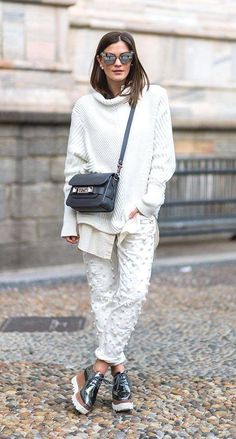 Total white look: jersey turtleneck, oversize blouse, jeans with details ripped and platform silver shoes