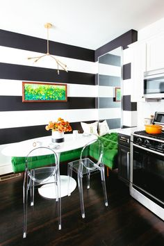 This white contemporary kitchen features a black-and-white accent wall as well as an eat-in area with a green banquette. Storage is provided by black and white cabinetry with white marble countertops, and a herringbone backsplash protects the wall.