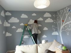 This simple but effective design was painted in a nursery for a newly married couple expecting their first child. They chose an elegant warm gender neutral grey as the back ground colour and we then painted simple white silhouettes of fluffy clouds and a blossom tree. To add a bit of vibrancy and fun to the mural we also included some brightly coloured simple birds.