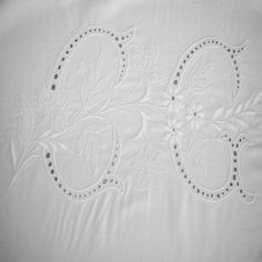 Drap en fil de lin blanc monogrammé CG. Taille du monogramme : 30x17cm. Le monogramme est travaillé sur toute la surface des lettres en broderie Richelieu et agrémenté de motifs fleuris au point de bourdon.Le drap est entièrement festonné sur le devant et sur un retour de 90 cm. Très beau jour de Venise également.Dimensions (largeur x longueur) : 200x300 cm.Monogram Size: 30x17cm. The monogram is worked over the entire surface of the letters Richelieu embroidery and ...