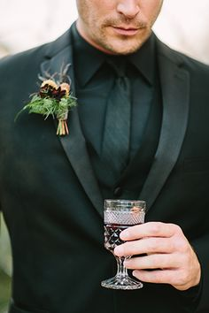 Spellbound Halloween Wedding Groom in a Michael Kors Black Tuxedo with Red Wine, Moody, spellbound wedding, dark and mysterious wedding, groom wearing all black, groom drinking wine, groom with wine glass, groom cocktail hour, michael kors tuxedo, all black tuxedo - A little bit to simple for me, but chique nontheless!