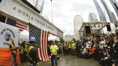 Iron workers attach a US flag to a signed beam as they join more than 1,000 fellow construction workers as the final steel beam is lifted by crane 977 feet in the air and placed atop 4 World Trade Center