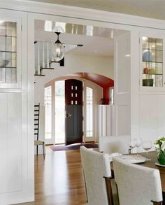 Staircase over a door is disguised as a hobbit-esque, rounded entryway, painted the same color from walls to ceiling. Cozy.