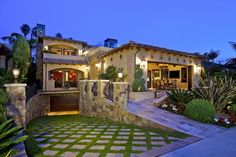 Stepping stones are carefully arranged in a neat pattern outside this Mediterranean-style home, adding texture and interest to the home's already unique landscaping. Natural stone walls and walkways complement the home's stucco exterior.