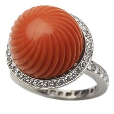 CARTIER Carved Coral and Diamond Ring  France  1950  A carved coral and diamond ring, designed as the fluted coral bead within a pave cut diamond surround, mounted in platinum, signed Cartier, Paris. Circa 1950, size 5.5.