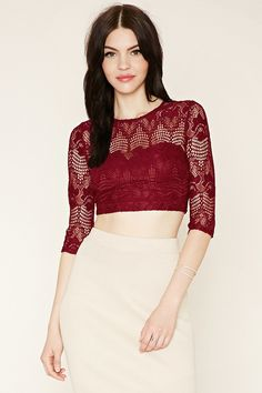 A sheer lace crop top featuring partial lining creating a sweetheart accent, round neckline, 3/4 sleeves, and loop-button closure.