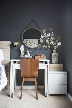 An at-home office isn't just for those who have a ton of square footage. All you need is an empty wall and a few accessories to make a delightful space you'll use. How can you achieve a small work space like this one? Make your furniture do more. When space is tight, you need pieces that multitask as well as you do. The desk above does it all — it's a bedside table, vanity, and workspace. With the help of a mirror and a vase of flowering branches, you barely even notice something as ordinary…
