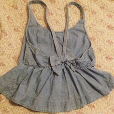 Hollister denim polkadot tank with bow This adorable light colored denim top has a bow in the back and a ruffle fitted waist. It's gently used, says medium but can fit small. Hollister Tops Tank Tops