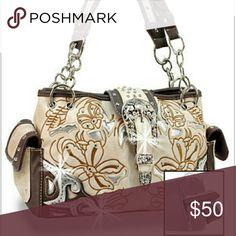Beige western embroidered concealed weapon handbag Beige western embroidered concealed weapon handbag.  Features a laser cut top layer accented with embroidery,  rhinestone accented trim. Back zipper pocket  for concealed weapon.  Dual carrying straps. 10 in drop length.  Zipper you opening.  Dual end pockets.  Fully lined interior includes zipper pocket and cell phone pouch. Zippered center divider, silver tone hardware. Metal stud feet. 13.5L x 8H x 4.5W Bags Satchels