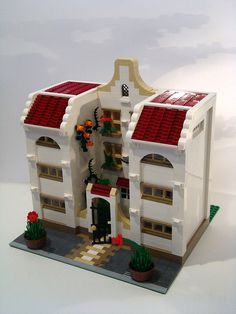 Lego mediterranean style house with arches, red tile roof and floral decor courtyard.