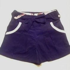 Sailor Corduroy Shorts Shorts are high waisted.  They are a dark navy corduroy with a floral cotton lining.  There is cream colored lace on the front pocket edge and camio buttons.  There is a hidden zip up closure in the back and a cordurory belt.  There are pleets in the front and cuffs on the hem.  Very 1940's vintage look.  Never been worn. ModCloth Shorts