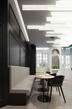 This bar area within a restaurant has black accent walls that match the black chairs, anddramatic lamella lighting on the ceiling. #RestaurantDesign #Lighting