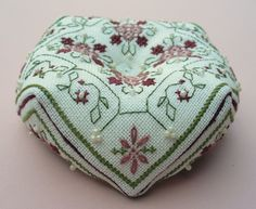 Example of a biscornu, 10 x 10 cm.  Biscornu (biscournu) is the name for a small, eight-sided pin cushion that became popular in the first decade of the twenty-first century. The word biscornu is derived from the French adjective biscornu, meaning irregular, skewed or strange.