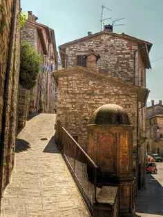 A narrow street and a well in the medieval town of Gubbio, Italy
