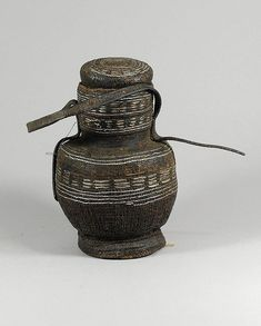 "OROMO (BORANA or GUDJII) ""chocho"" container. (22,8 cm). Used to hold milk to be serve to guests or kept for special occasions. They are tightly woven of twine, then steeped with fat or resinous gum to make them waterproof, and decorated with metal wire."