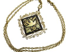 A lovely Damascene pendant showcasing a nature inspired design of flowers and a sweet bird with a decorative lace trim dangles from a 24 inch gold chain in this attractive accessory.